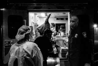 COVID .A Los Angeles Fire Department crew  amid a sleepless 24-hour shift  gives a report to a County-USC emergency physician on the ambulance ramp. (Dr. Scott Kobner . Los)